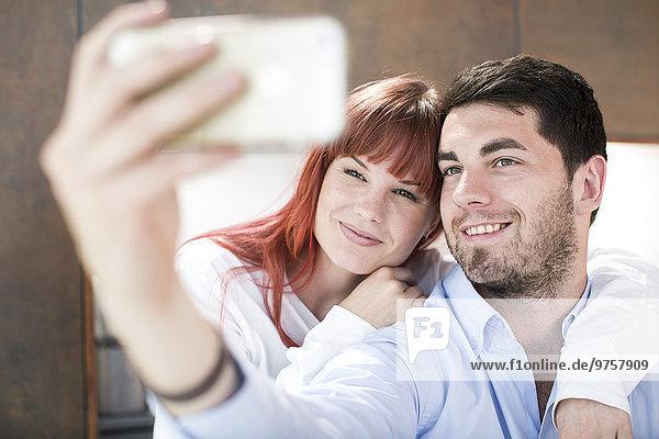 Ein Paar in der Küche nimmt einen Selfie.
