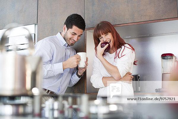 Glückliches Paar in der Küche mit Apfel und Tasse Kaffee