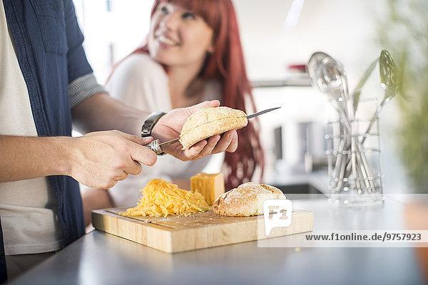 Paar in der Küche Brot mit Käse zubereiten
