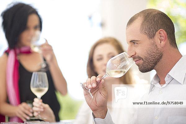 Weißwein riechender Mann bei einer Weinprobe