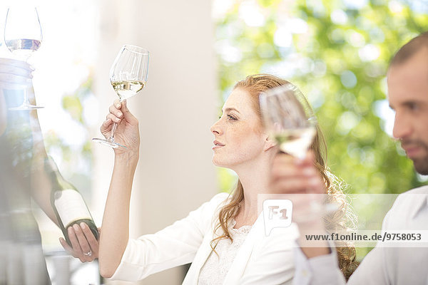 Woman examining white wine on a wine tasting session