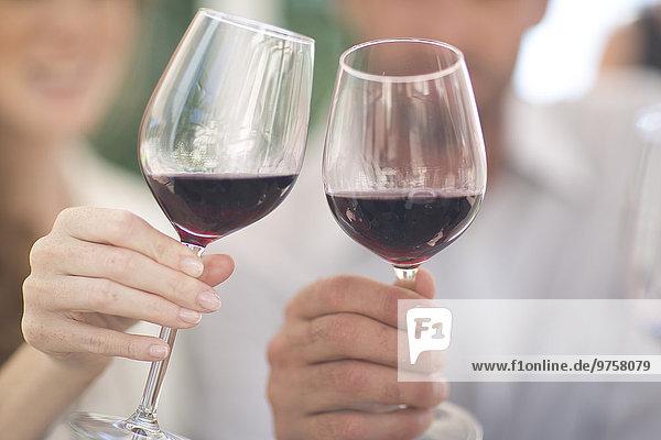 Hände halten Gläser mit Rotwein