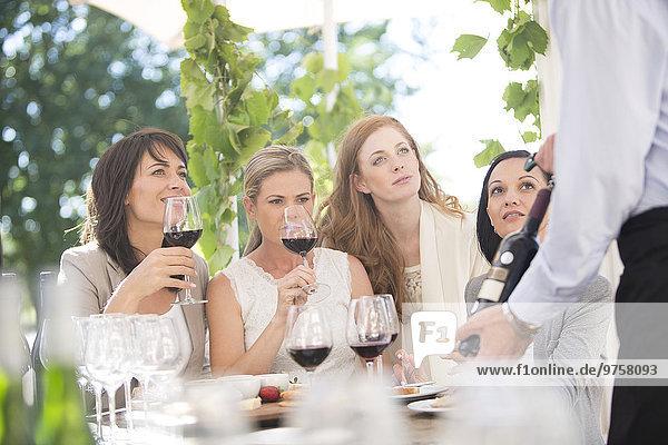 Kellnerin präsentiert den Frauen eine Flasche Rotwein bei einer Weinverkostung.