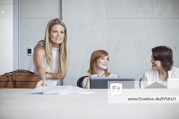 Drei Geschäftsfrauen bereiten sich auf eine Besprechung im Konferenzraum vor