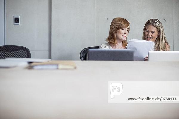 Zwei Geschäftsfrauen mit Laptop und Unterlagen im Konferenzraum