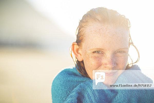 Porträt eines lächelnden Mädchens am Strand in ein Strandtuch gehüllt