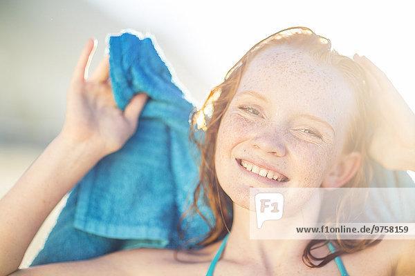 Porträt eines lächelnden Mädchens am Strand  das seine Haare mit einem Strandtuch trocknet.