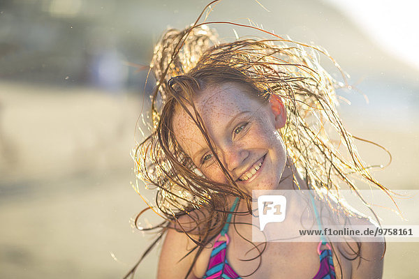 Mädchen am Strand lächelt und schwingt ihre Haare in den Wind.