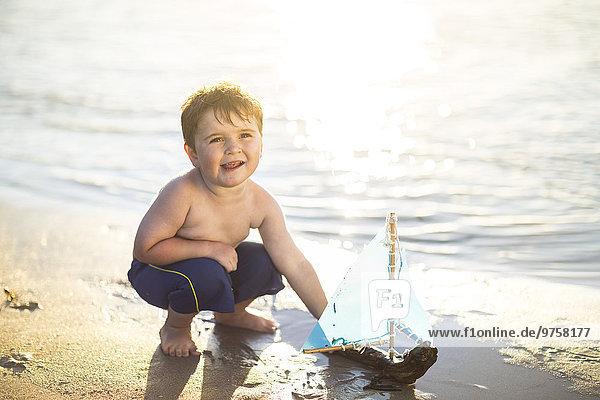 Junge am Strand spielt mit einem Spielzeug-Holzboot im Wasser Junge am Strand spielt mit einem Spielzeug-Holzboot im Wasser