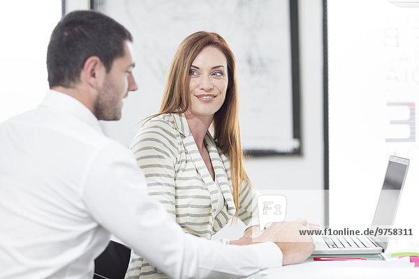 Geschäftsfrau und Geschäftsmann im Büro bei der Arbeit am Laptop