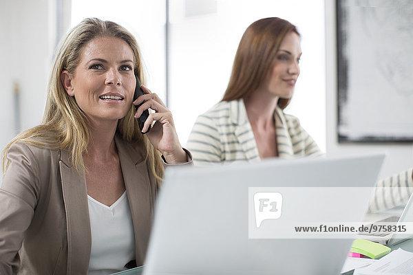 Zwei Geschäftsfrauen im Büro mit Laptop und Telefon