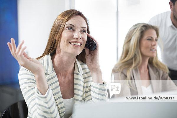 Geschäftsfrau im Büro beim Telefonieren