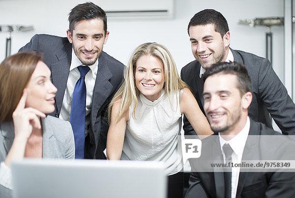 Geschäftsleute im Büro mit Blick auf den Laptop