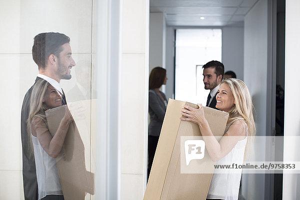 Geschäftsfrau trägt große Kiste durchs Büro