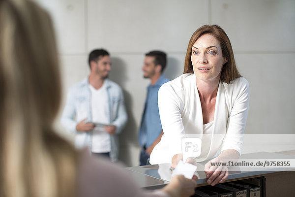 Geschäftsfrau im Gespräch mit der Rezeptionistin am Schalter