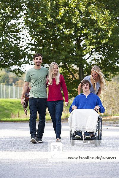 Junger Mann im Rollstuhl mit Freunden