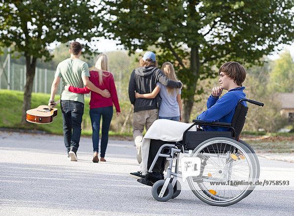 Zwei junge Paare Arm in Arm und junger Rollstuhlfahrer allein