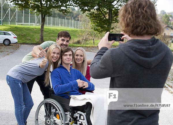 Junger Mann fotografiert seine Freunde mit dem Smartphone