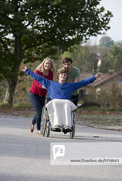 Junges Paar mit Freund im Rollstuhl sitzend