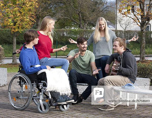 Vier junge Leute  die Gitarre hören