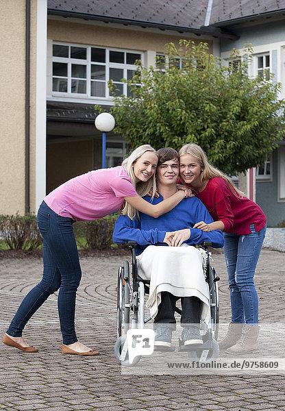 Teenagermädchen und junge Frau mit ihrem Freund im Rollstuhl sitzend