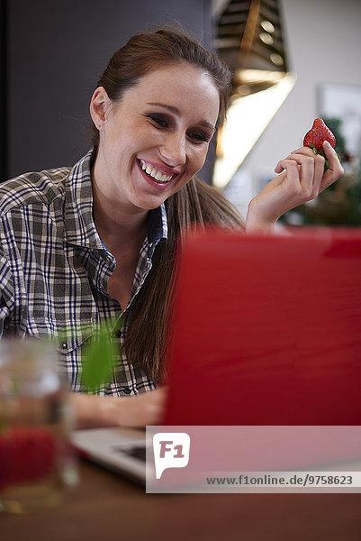 Schwangere Frau mit Laptop zu Hause  Obst essen