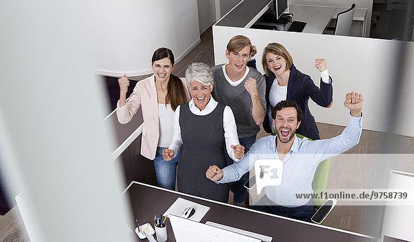 Fröhliches Geschäftsteam feiert am Schreibtisch im Büro