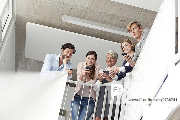 Geschäftsleute mit Mobiltelefonen im Treppenhaus