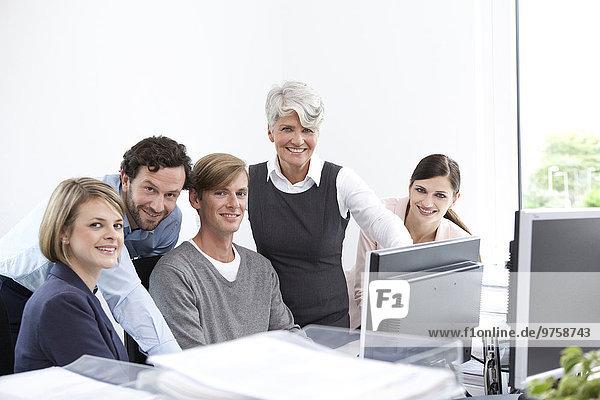 Lächelndes Geschäftsteam bei der Arbeit am Computer im Büro