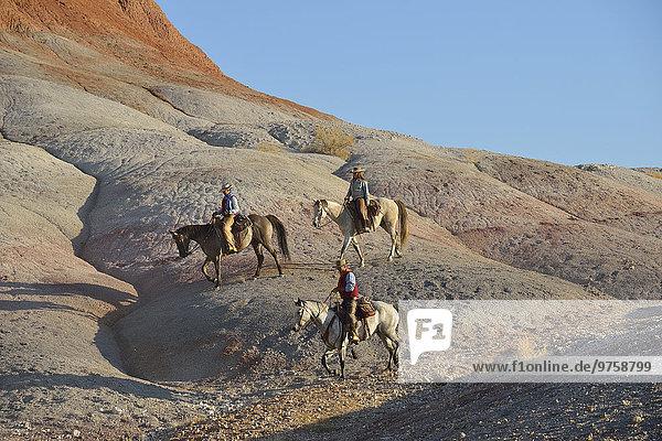 USA  Wyoming  zwei Cowgirls und ein Cowboy beim Reiten in Badlands