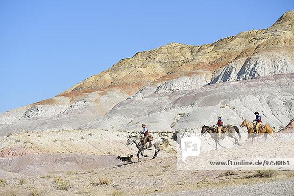 USA  Wyoming  zwei Cowboys und Cowgirl beim Reiten in Badlands