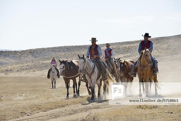 USA  Wyoming  Cowboys und Cowgirl führende Pferde in Badlands