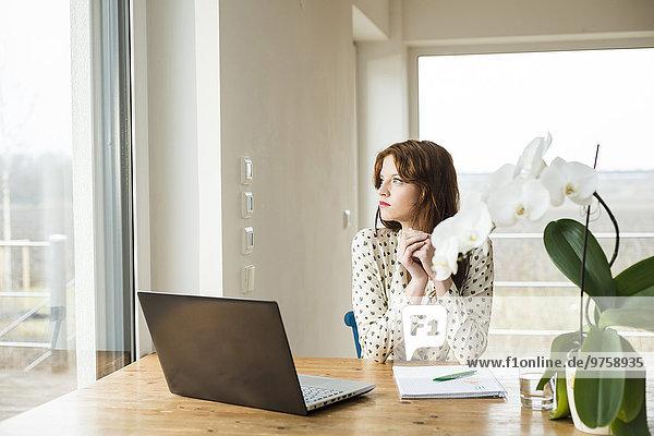 Junge Frau mit Laptop am Holztisch mit Blick aus dem Fenster