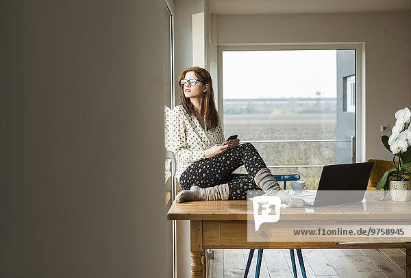Junge Frau mit Handy auf Holztisch sitzend
