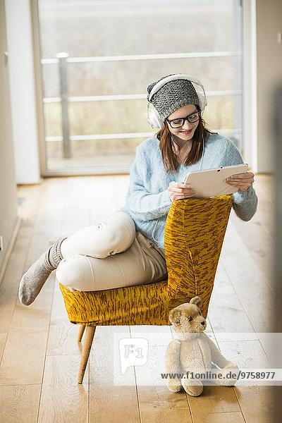 Lächelnde junge Frau sitzend auf Stuhl mit digitalem Tablett und Kopfhörer