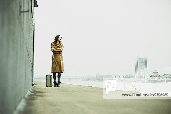 Junge Frau mit Koffer am Flussufer