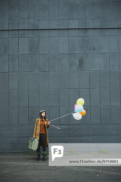 Junge Frau mit Koffer mit Ballonhülle