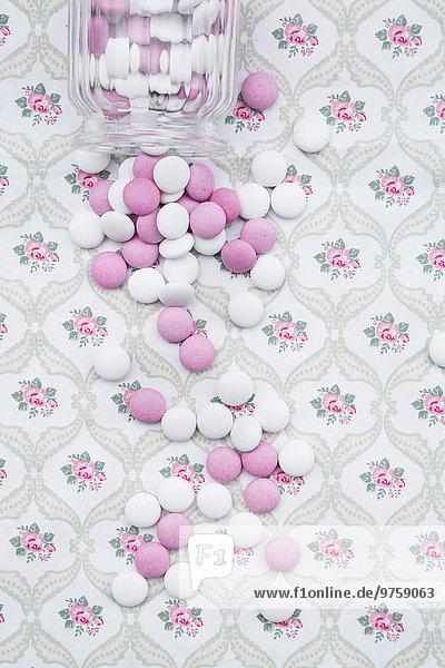 Rosa und weiße Schokoladenknöpfe auf Blumenmusterstoff