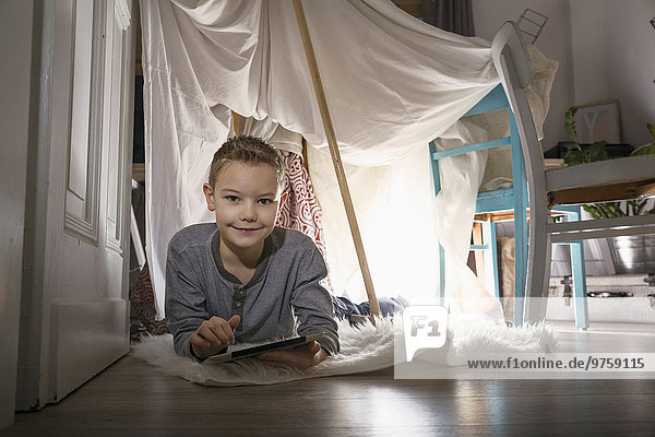 Junge digitales Tablett liegend im selbstgebauten Zelt zu Hause am Abend