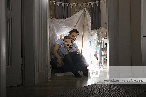 Vater und Sohn sitzen abends im selbstgebauten Zelt zu Hause mit Hilfe eines digitalen Tabletts.