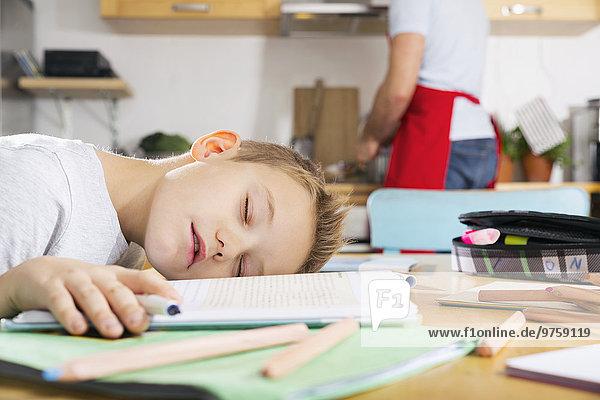 Junge sitzt am Küchentisch und schläft auf seinem Schulbuch.
