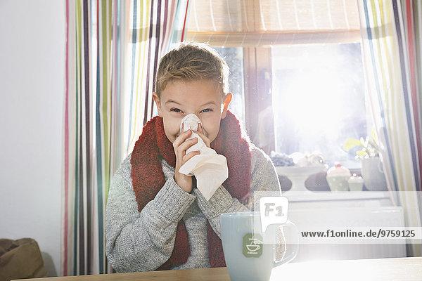 Junge sitzt in der Küche und schnäuzt sich die Nase.
