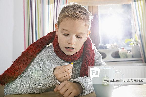 Junge sitzt in der Küche und schaut auf die Tafel.
