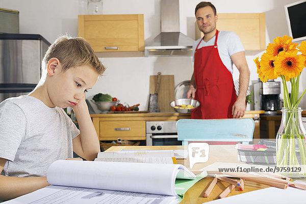 Junge sitzt am Küchentisch mit seinen Hausaufgaben