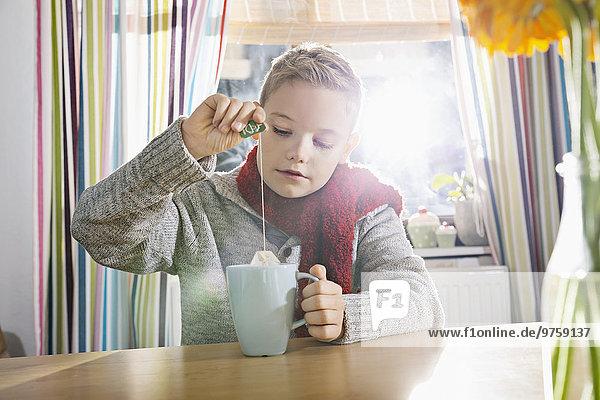 Junge mit einem kalten Sitzen in der Küche mit einer Tasse Tee