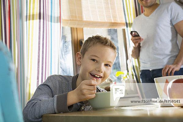 Porträt eines lächelnden Jungen am Frühstückstisch mit Granola