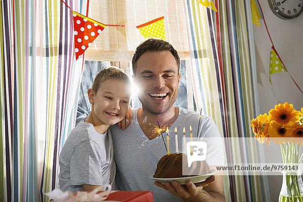 Vater und Sohn mit Geburtstagskuchen