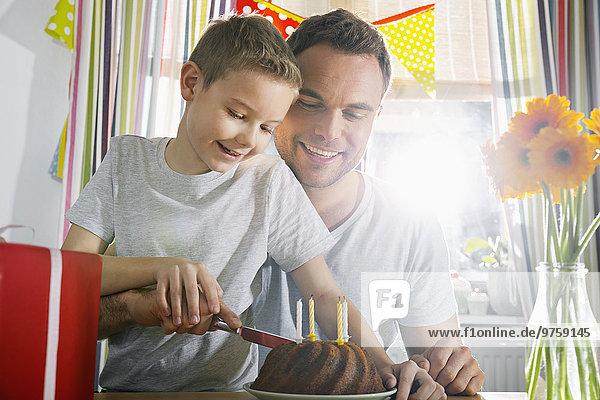 Vater und Sohn schneiden Geburtstagskuchen