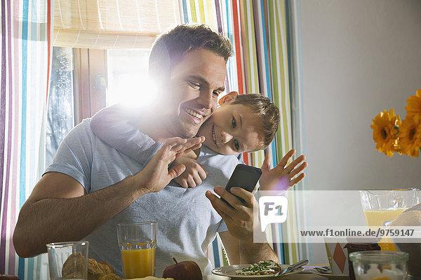 Vater und Sohn sitzen am Frühstückstisch und nehmen einen Selfie.