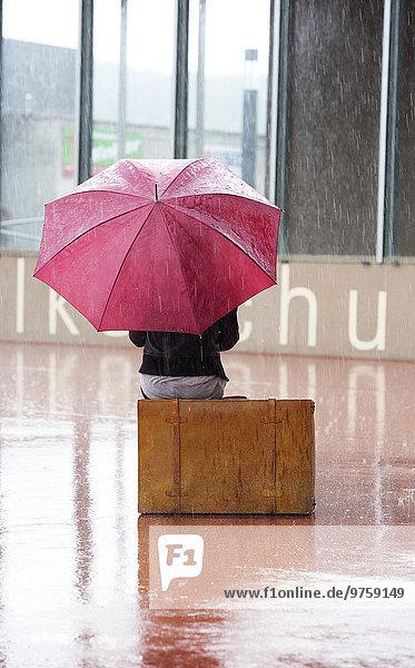 Österreich  Thalgau  Teenagermädchen mit rotem Regenschirm auf dem Koffer sitzend im Regen